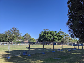 The same park from the last photo, with still dry grass and a temporary fencing around, but the sky is now bring vibrant blue with white horizon, and the grass is harshly lit by the sun.