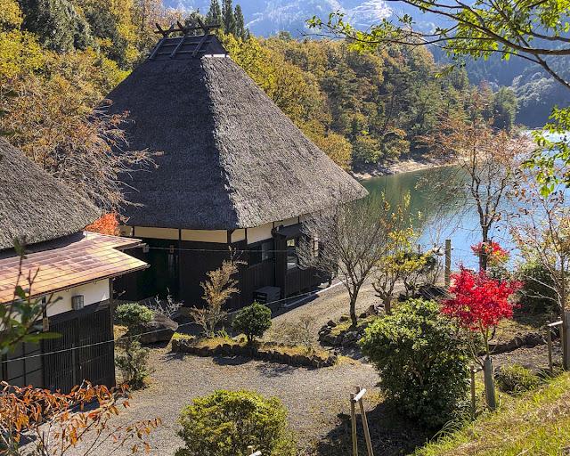 湖のほとり、茅葺きの家、庭に紅葉が一本