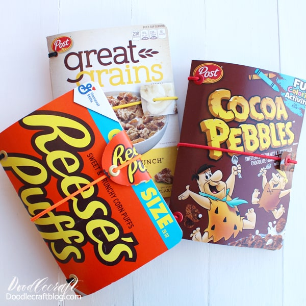 """Cereal Box Refillable Notebooks  These awesome notebooks hold paper folded in half--and they are made of old cereal boxes. The biggest part is the elastic...1/4"""" flat elastic from Walmart is under $3, so if you can't find anything around the house, you can purchase some and make several.   I asked my neighbors if they had any cereal boxes, because I don't buy cereal in boxes very often. I got exactly what I needed! Any lightweight cardboard box will work if it's big enough, check the cupboards and rock what you've got!"""