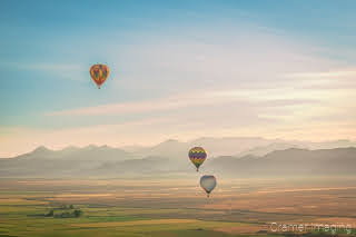 Cramer Imaging's fine art aerial photograph of three hot air balloons flying over a field in Panguitch Utah with a blue partly cloudy sky