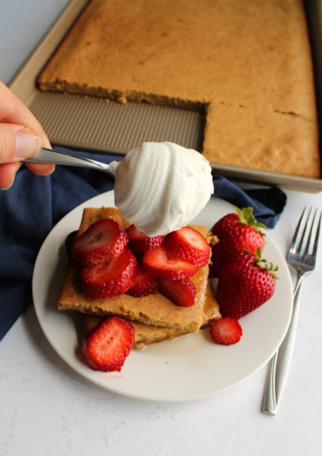 hand dolloping maple whipped cream on top of stack of sheet pan pancakes