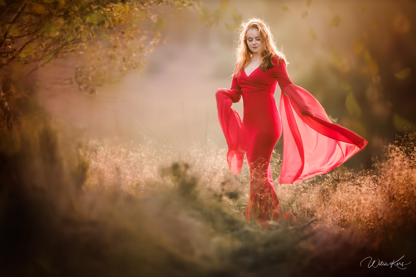 Canon Fine art portrait of Dutch photographer Willie Kers of a young red headed woman in a red wedding dress standing in the field during sunset in  Apeldoorn