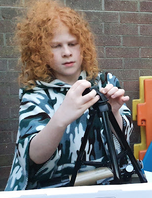 Boy assembling telescope and tripod outdoors on glass table