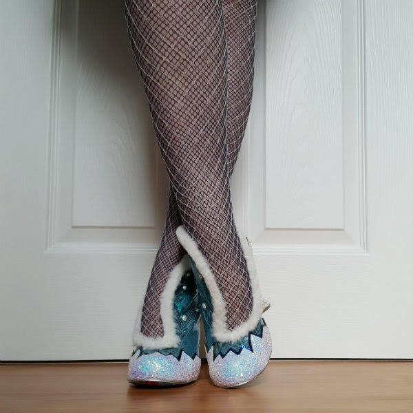 crossed legs with layered fishnet tights and white glitter and fur trimmed shoes