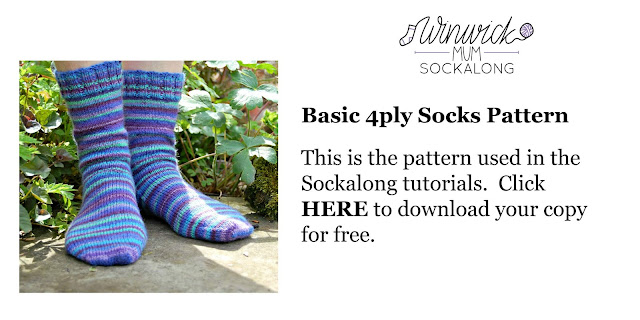 A pair of blue, green and purple striped socks modelled on feet.  The model is standing on a stone slab surrounded by plants.