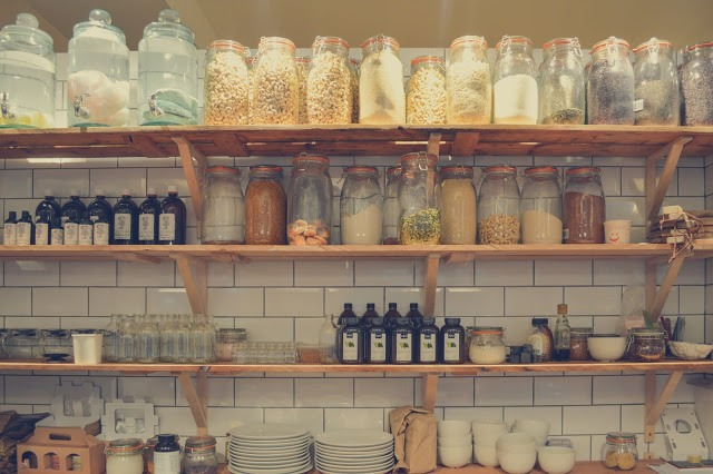 A shelf with glass jars filled with dry food ingredients