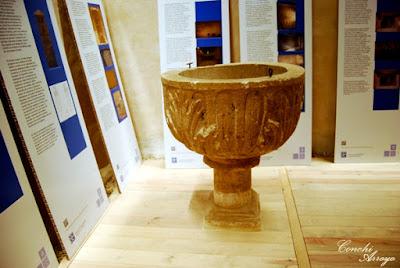 Pila bautismal en el interior de la iglesia de San Miguel de San Esteban de Gormaz y paneles con toda la información necesaria para conocer a fondo este monumento.