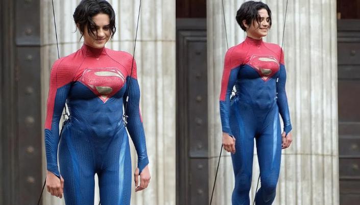 """Imagem: Supergirl no set de gilmagem, suspensa por cabos. Ela é uma mulher branca de cabelos curtos e pretos, e seu uniforme é estilo collant, azul, com a região dos ombros em vermelho. E com o símbolo do """"S"""" no peito."""