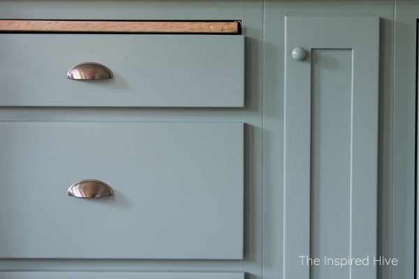 SW Privilege Green cabinets with brass pulls and wood knobs