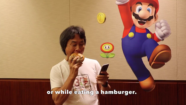 Shigeru Miyamoto eating hamburger with one hand playing Super Mario Run