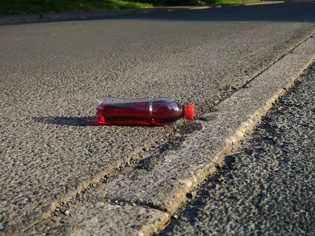 Plastic bottle of red liquid left on tarmac pavement.
