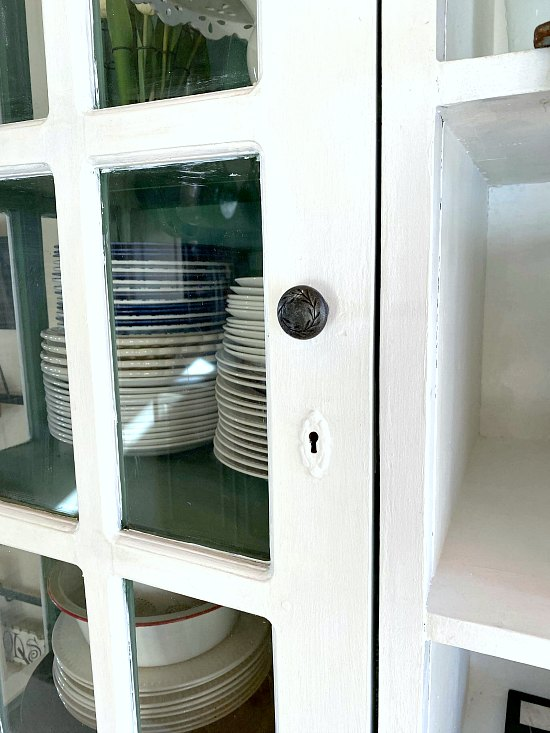 White farmhouse hutch with glass doors.