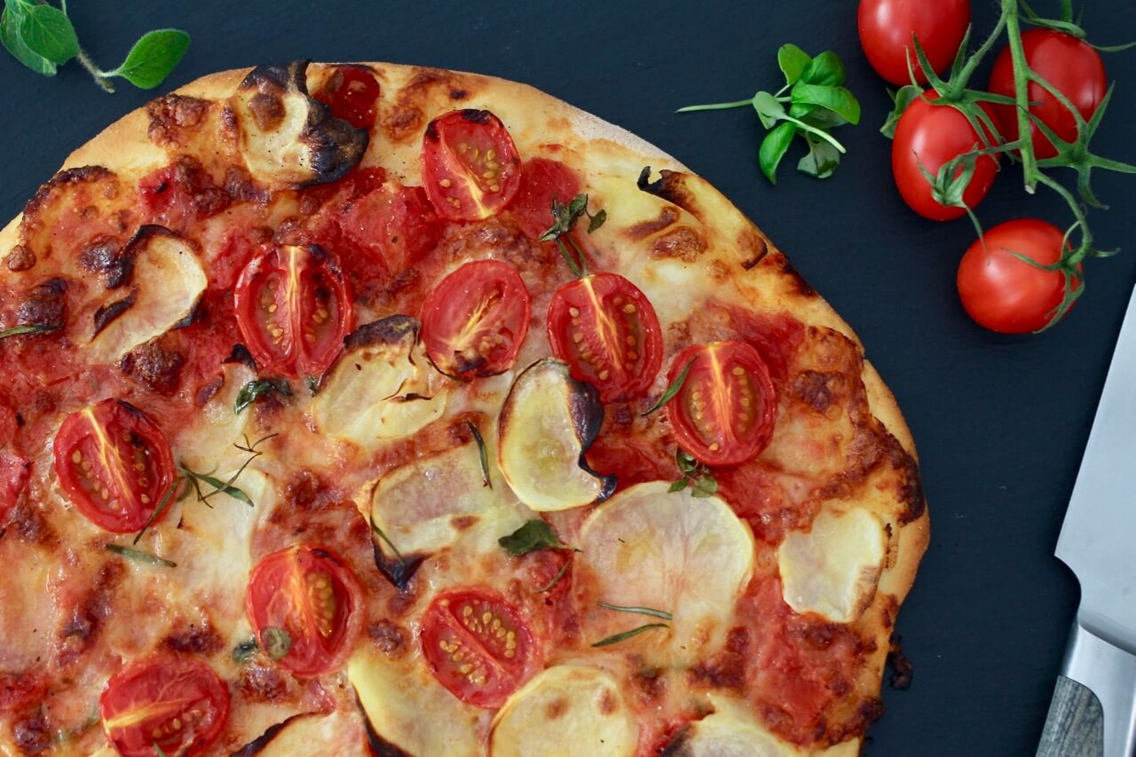 Pizza mit Chips und Cherrytomaten