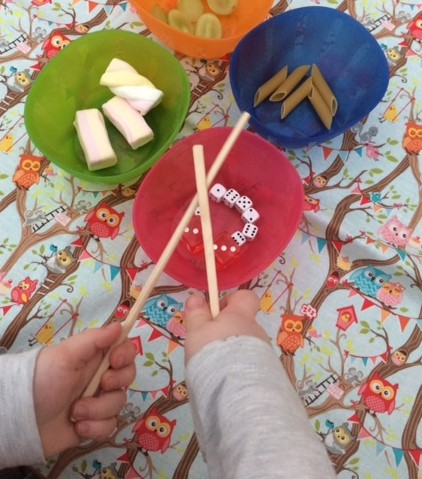 A selection of bowls filled with different items and little hand using chopsticks, trying  to pick them up
