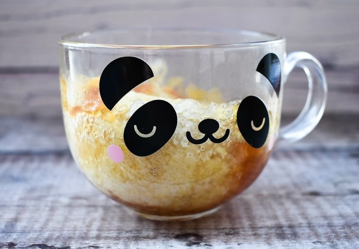 Microwave Golden Syrup Sponge Pudding in a glass mug with a panda face