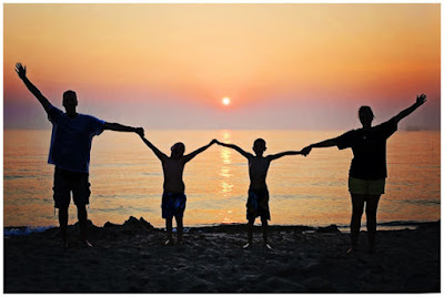 """Piirretty """"perhe"""" (nainen, mies ja kaksi lasta käsikkäin) keskittyneenä auringonlaskuun utuisella taivaanrannalla."""