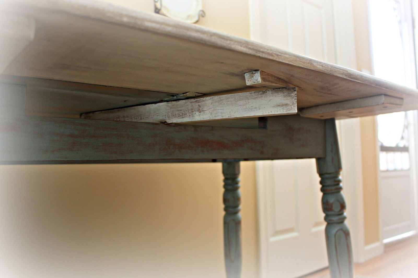 The wood support bars underneath swivel to extend the table leaves.