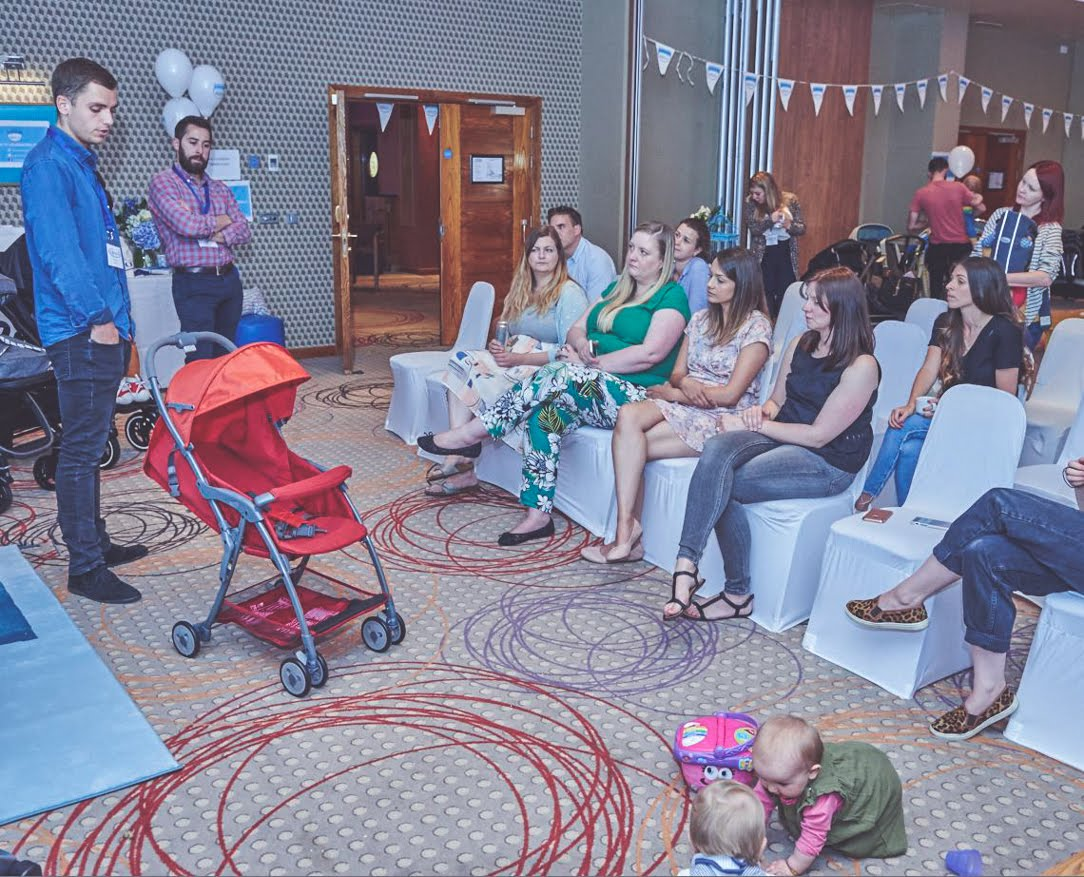 presentation of Graco red stroller with bloggers seated on white chairs