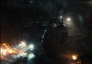 Batman standing on top of his enormous Dark Knight Returns-style tank with a group of tied-up people sitting in the headlights below