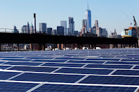 The Manhattan skyline peers over a rooftop covered with solar panels at the Brooklyn Navy Yard in New York. (Credit: Associated Press) Click to Enlarge.