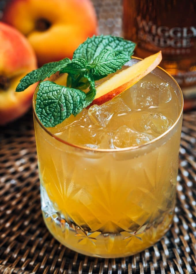 This icy peach bourbon cocktail is the perfect refreshing sip on a hot summer night! Inspired by my trip to Wiggly Bridge Distillery in York,