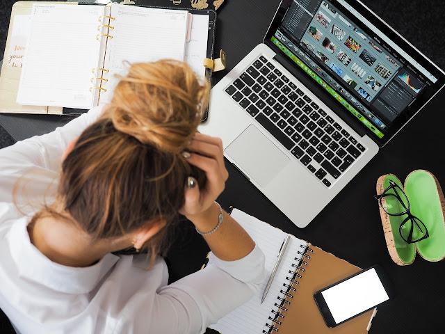 Femme déprimée à son bureau, devant son ordinateur.