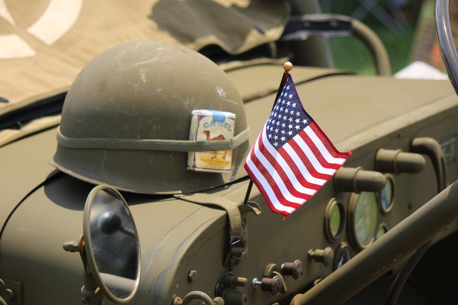 world war 2 helmet and small american flag lies on military jeep to illustrate blog post about u.s. army movies