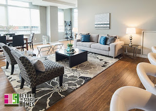Staged living room - grey sofa and chairs with flower print area rug, open concept