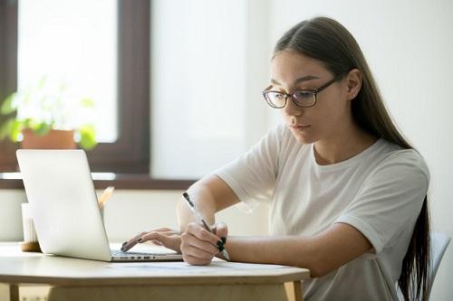 estudante jovem fazendo faculdade a distância em casa com notebook e anotando