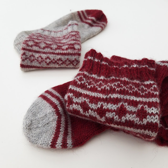 Two colourwork socks on a white background - one is maroon with grey, the other is grey with maroon