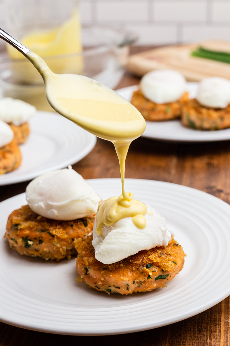Closeup photo of a spoon drizzling hollandaise sauce over the poached eggs on Keto Salmon Eggs Benedict.