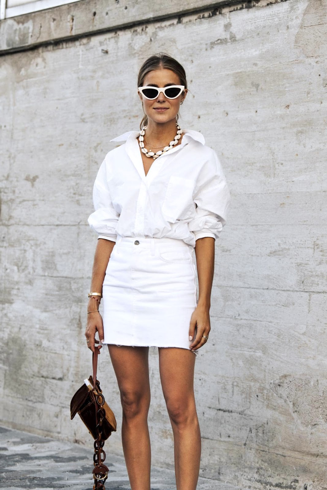 All-White Summer Outfit — Scandi-girl street style with cat-eye sunglasses, shell necklace, button-down shirt, and denim skirt
