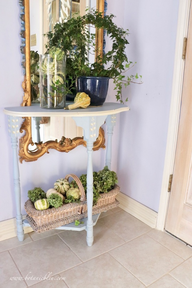 Fall Foyer decorated with green gourds, hydrangeas, ivy wreath on blue demilune table