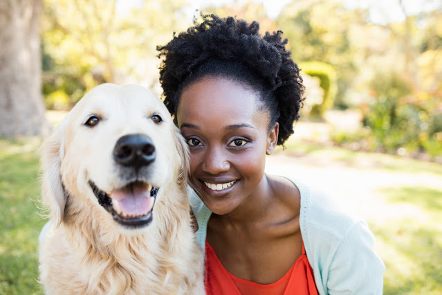 Diversity initiatives in animal behavior & dog training. Photo shows young black woman with happy Golden Retriever