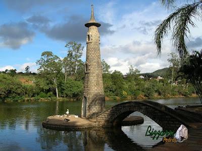 Ponte de pedra folheta no lago com a torre de pedra.