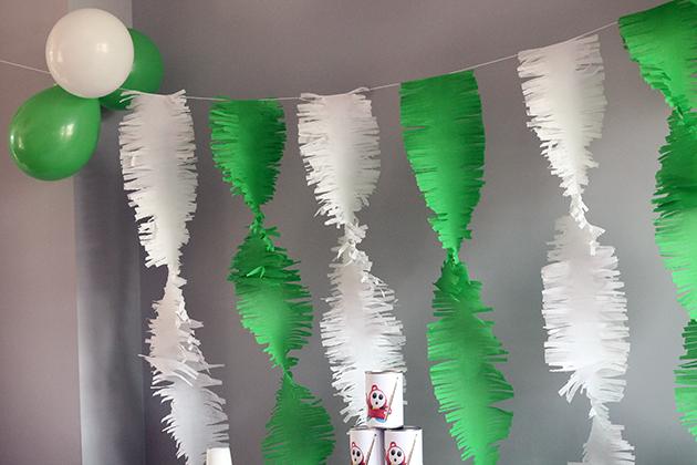Achter de tafel hingen brede slingers van wit en groen crêpe papier. Die heb ik gemaakt door een pak wit en een pak groen crêpe papier in drie brede stroken te knippen en in deze stroken franjes te knippen (iedere kant ongeveer 1/3 inknippen). Daarna heb ik ze met een flinke overlap over de gespannen draad gehangen en ze een paar keer rondgedraaid (alle stroken even vaak!) en onderaan vastgezet met een plakbandje.