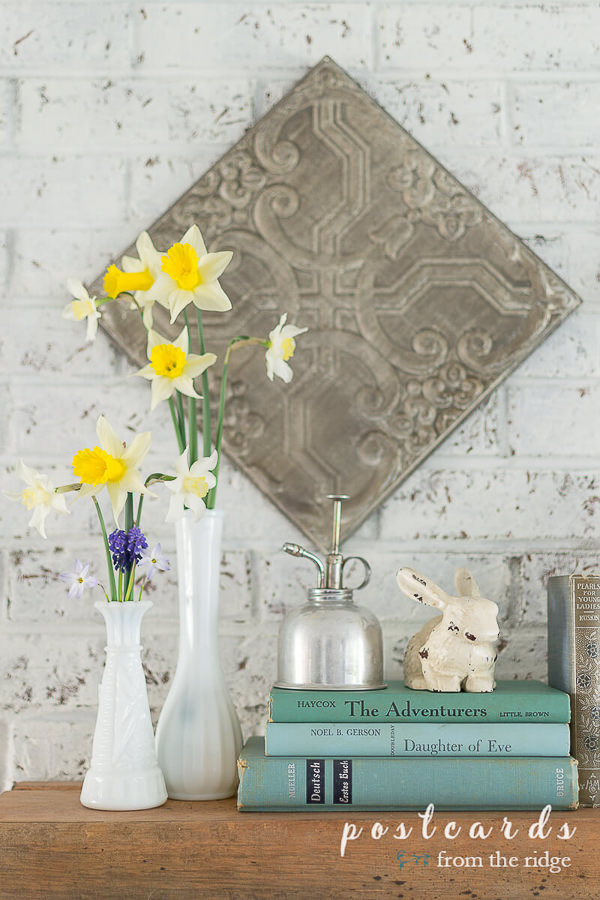 daffodils and grape hyacinths in vintage white milk glass vases with vintage books