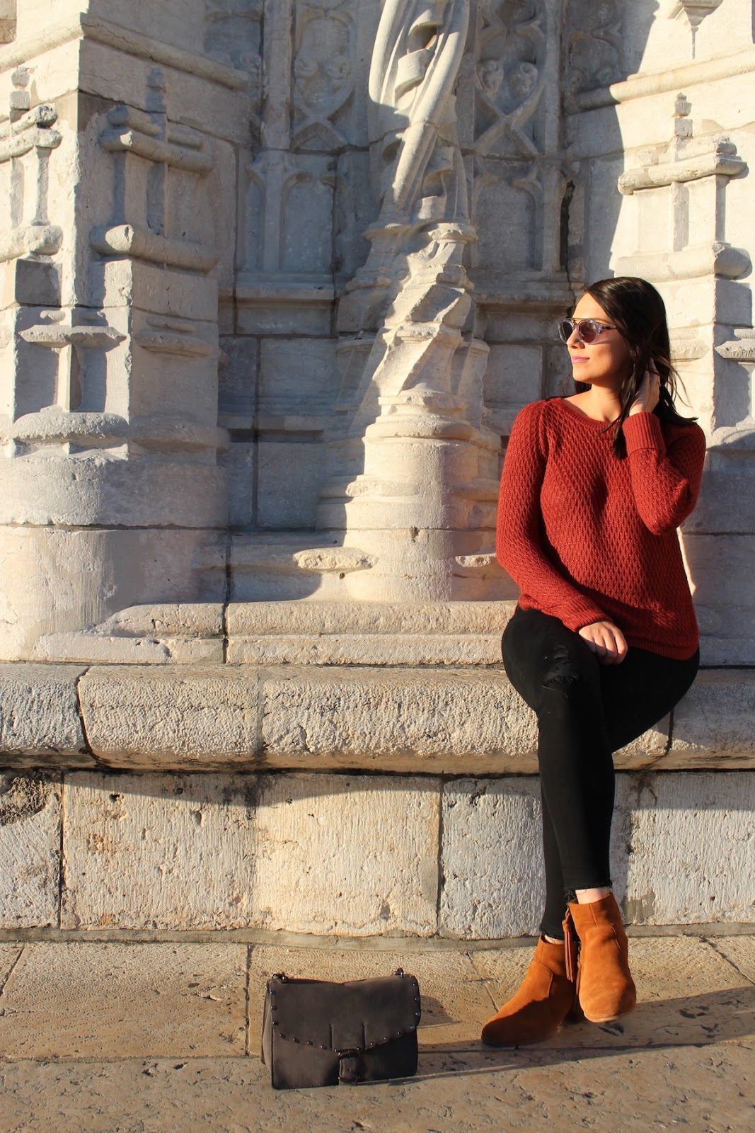 This photo shows me in my fall outfit (red sweater, black jeans, sunglasses and heeled booties) sitting on the steps of the Lisbon Cathedral in Lisbon, Portugal.