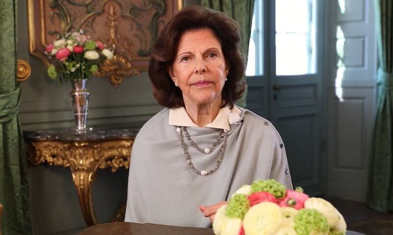 The symposium was organized by Harvard University. Queen Silvia of Sweden wore a gray cape with side buttons. Pearls necklace