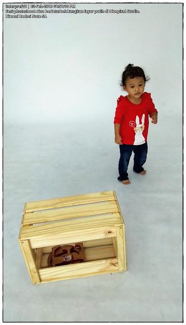 gambar seorang kanak-kanak 2 tahun bergambar di depan layar putih.