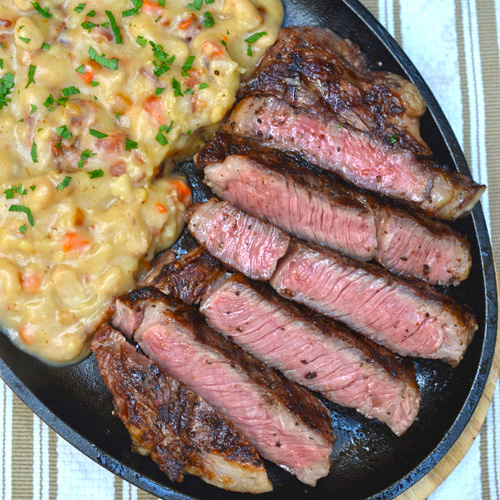 Certified Angus Beef ribeye steak with white beans and bacon