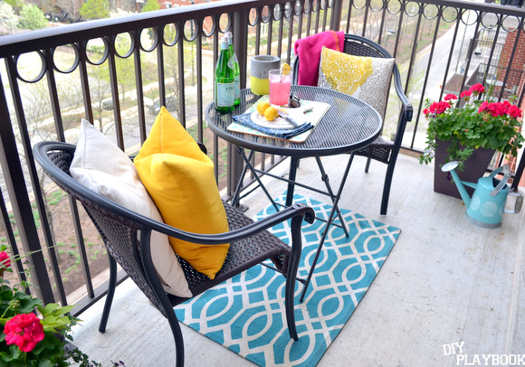 And here is is with a few throw pillows, a fun new blue and white rugs and a few potted plants! What do you think of our new summer balcony decor?