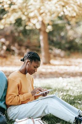 Mujer escuchando podcast, en un parque.