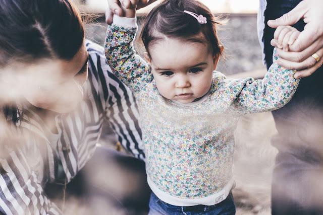 Kleines Mädchen an der Hand ihrer Eltern