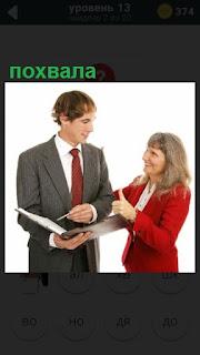 женщина хвалит мужчину в костюме с документами
