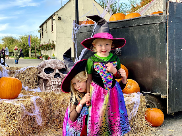 2 sisters dressed as colourful witches in front of a halloween display at Marsh Farm