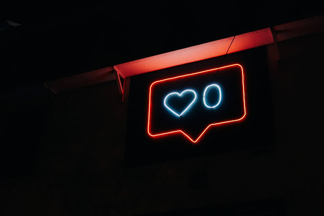 a text bubble with a heart inside in neon lights in a completely black background