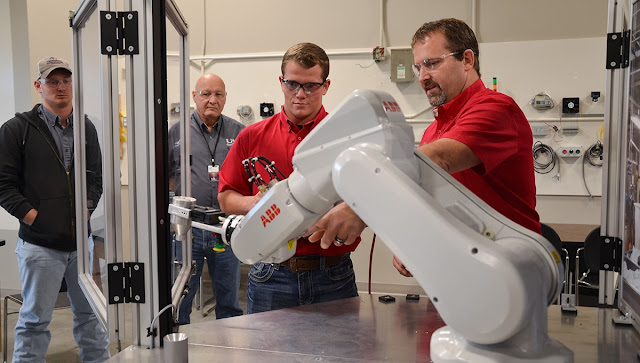men stand by a robotic arm