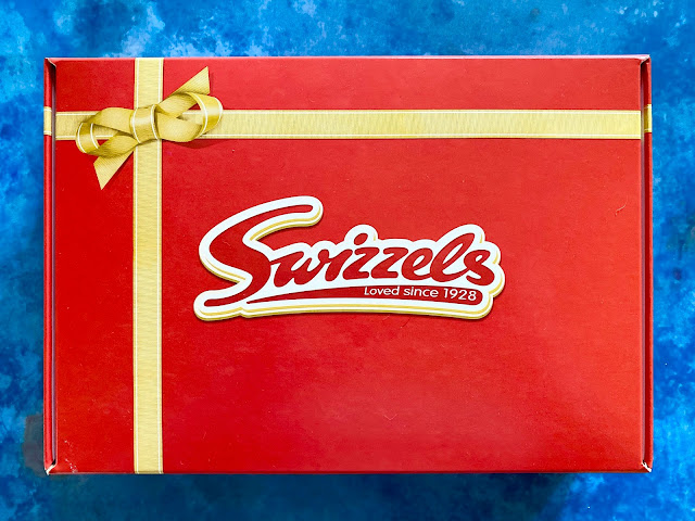 Swizzels cardboard sweet hamper box. It is bright red with a printed on gold ribbon and the Swizzels logo