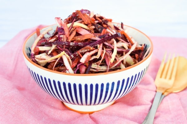Easy Balsamic Beet Slaw in a white a blue stripy bowl on a pink napkin
